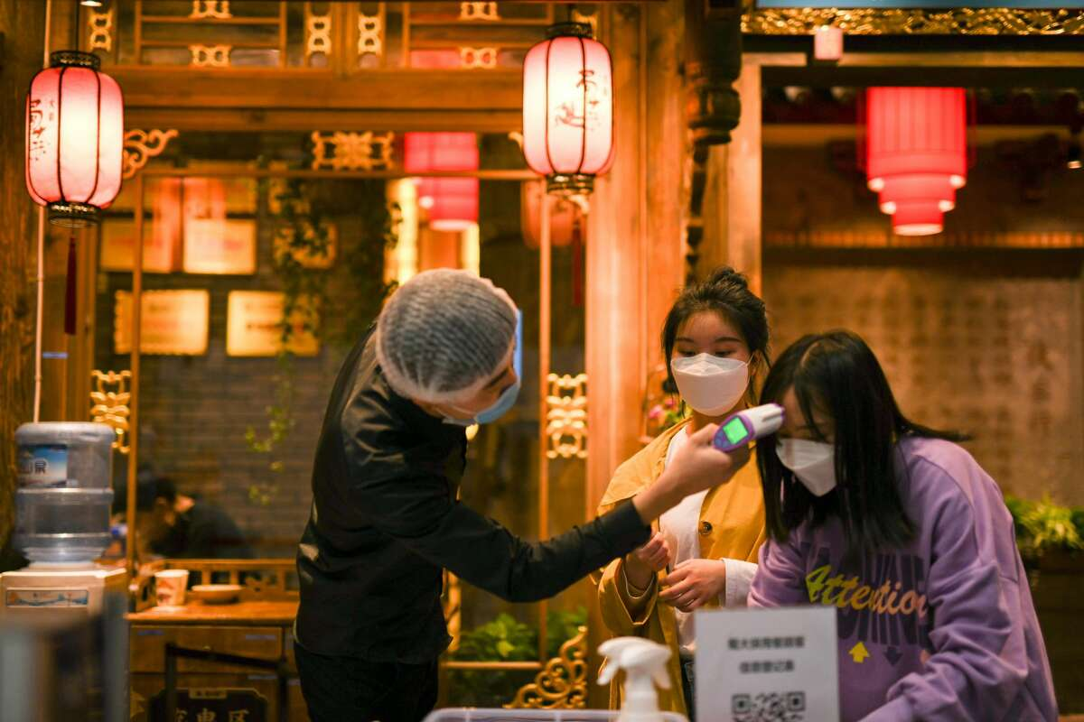 Temperature checks Temperature checks have become part of the routine before entering a restaurant. Here, a customer registers as a staff member checks her body temperature at the entrance of a restaurant in Chengdu, southwest China's Sichuan Province on March 21, 2020.