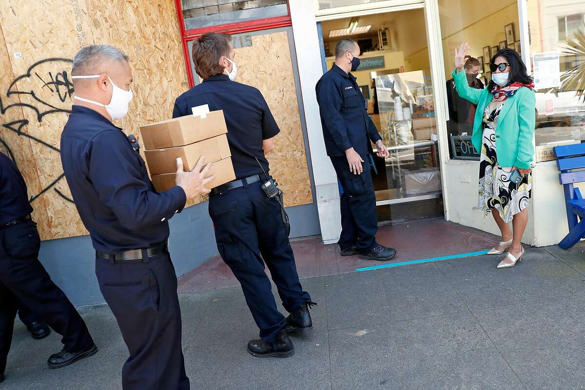Commercial real estate broker Normita Smith waves at members of SF Fire Department members from Station 34 and Truck 14 while Smith donates bakery goods to the first responders at Butter Love Bakeshop in San Francisco, Calif., on Tuesday, April 21, 2020.