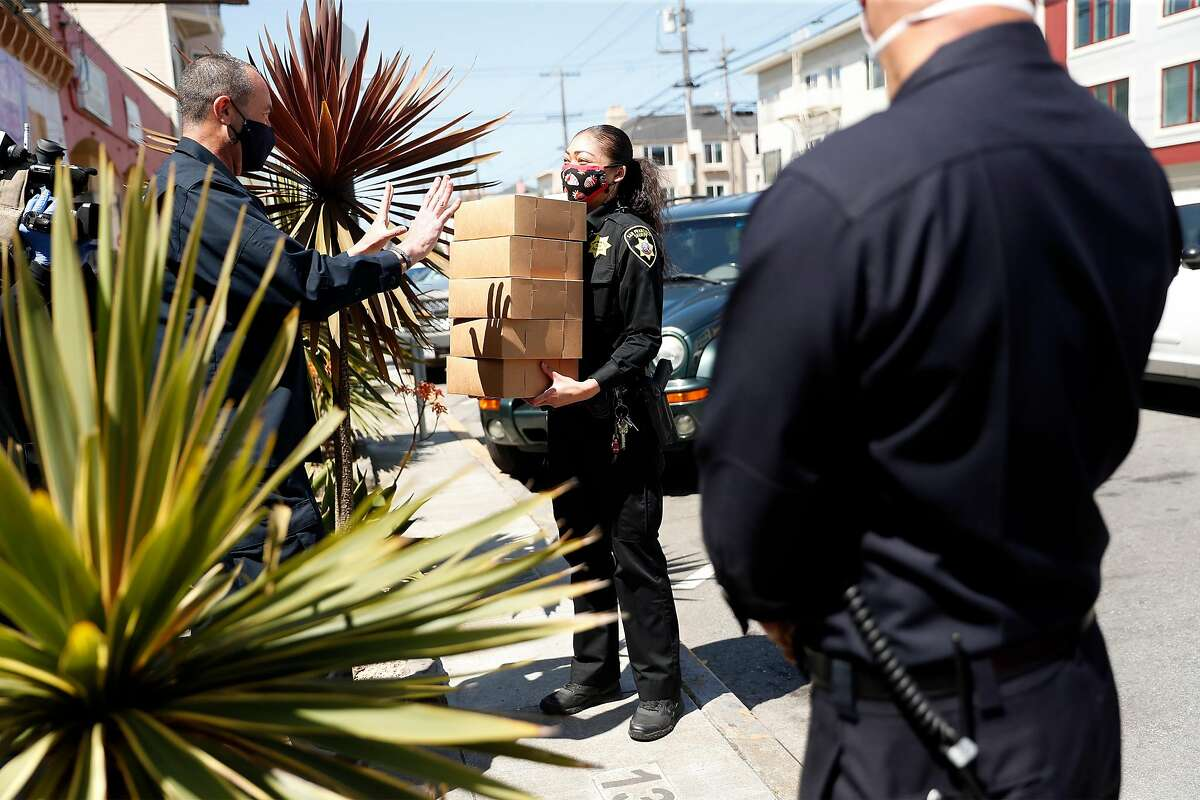 San Francisco Fire Dept. Lt. John Baxter hands pies to SF Sheriff Department's Marielle Elliott after they were donated by commercial real estate broker Normita Smith at Butter Love Bakeshop in San Francisco, Calif., on Tuesday, April 21, 2020.