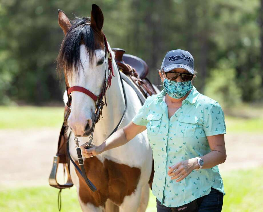 Alisa Jones prepares her horse, Sunny, for a ride around W.G. Jones State Forest in Conroe, Monday, April 20, 2020. Jones has been riding horses for over 50 years. Photo: Gustavo Huerta, Houston Chronicle / Staff Photographer / Houston Chronicle © 2020