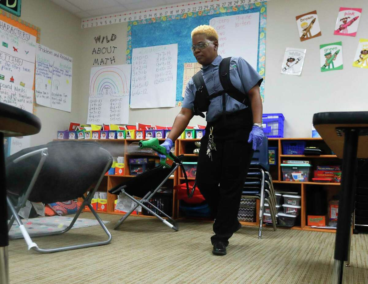 Esther Robinson, Montgomery ISD's unit director for education management services, uses a cleaning solution to disinfect Lincoln Elementary School in this March photo. School districts across Texas are expected to roll out their health and safety guidelines in the coming weeks after state officials left many decisions to local leaders Tuesday.