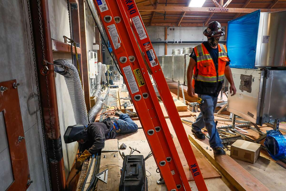 A welder (left) solders material as he works to help build the new Kaiser Permanente Laboratory in Berkeley, California on Monday, April 20, 2020. The construction of the $14 million laboratory in Berkeley will be capable of processing 70,000 Covid-19 tests a week when it opens in early June.