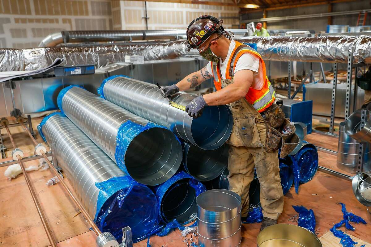 Construction worker Jon Persico helps build the venting system at the new Kaiser Permanente Laboratory in Berkeley, California on Monday, April 20, 2020. The construction of the $14 million laboratory in Berkeley will be capable of processing 70,000 Covid-19 tests a week when it opens in early June.
