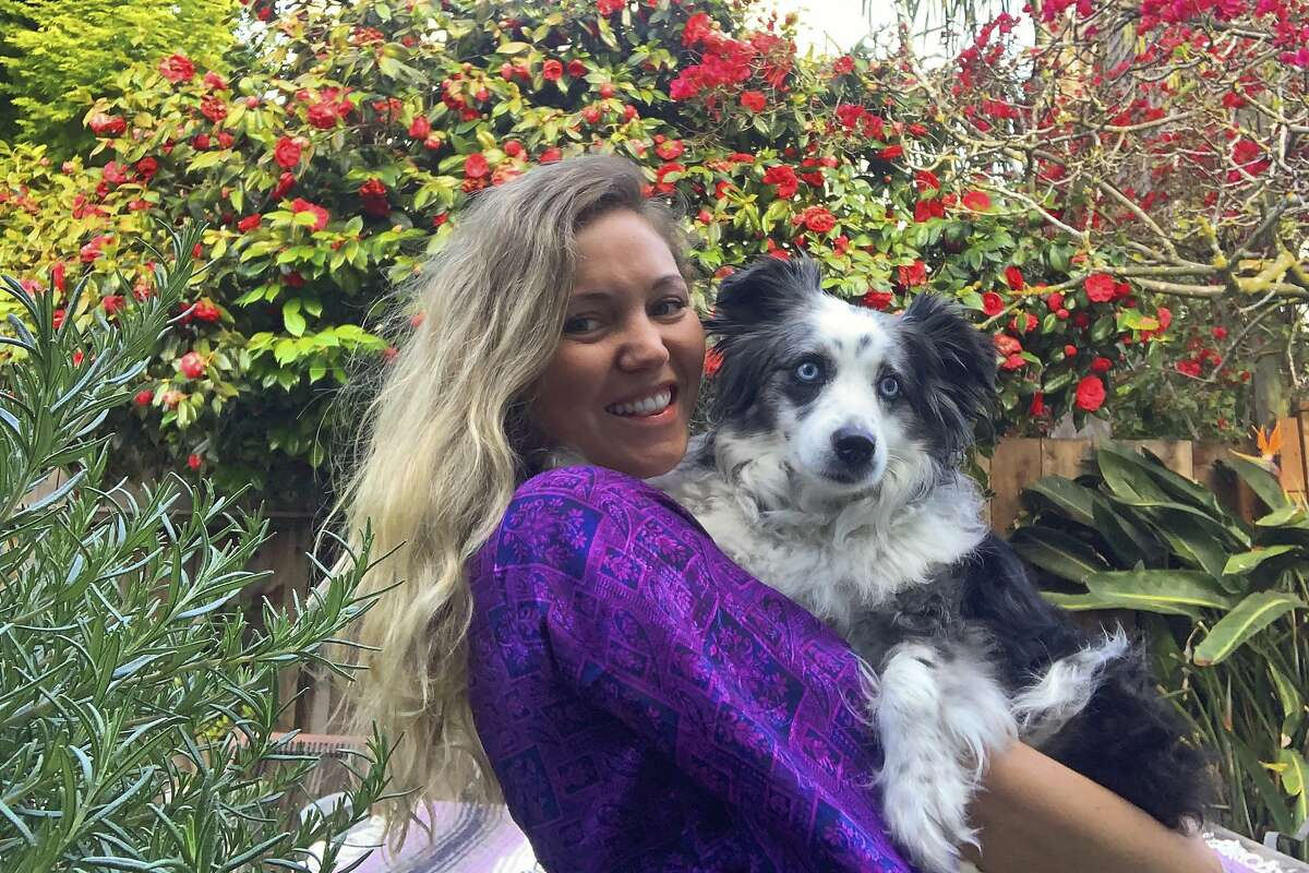 In this photo provided by Emilie Talermo, she is shown after being reunited with her six-year-old dog Jackson in San Francisco, on Tuesday, April 21, 2020. Back in December, a distraught Talermo hired a plane to fly a search banner for her stolen dog. On Monday, the dog was found 370 miles (600 kilometers) away in Southern California. Talermo, 31, said Tuesday she received a call from an animal shelter in Palmdale telling her someone had just dropped off a blue-eyed mini Australian shepherd and that a scan of the dog's microchip had turned up her phone number. (Courtesy of Emilie Talermo via AP)