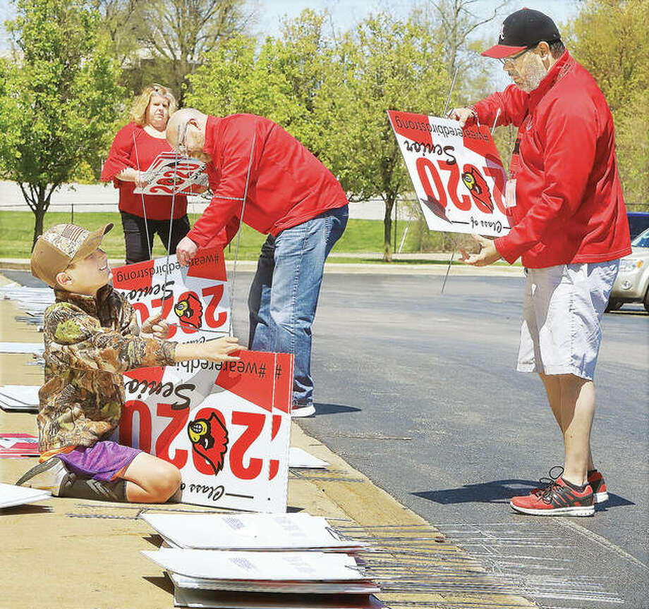 Alton High School Assistant Principal Michael Brey, right, and other district staff members had a little help in front of the school Tuesday from 11-year-old Devin Michalski, left, as they were preparing signs for staff members to put in the front yards of seniors in the district. The remainder of the school year has been canceled by Gov. J.B. Pritzker because of the COVID-19 outbreak.
