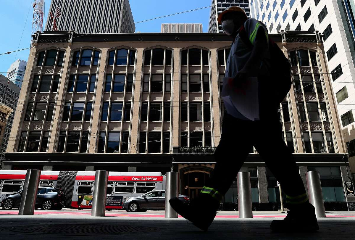 A pedestrian walks in front of 440-450 Mission Street in San Francisco, Calif., on Tuesday, April 21, 2020. Salesforce purchased 440-450 Mission St. for $145 million in March, a huge sum for a relatively small building, at more than $2,500 per square foot. But location matters: The site is next to Salesforce-owned 50 Fremont and across the street from Salesforce Tower. Could a tower be built on the site? The deal may be one of the last for the 2011-2020 real estate boom, as offices have been shuttered and it?s unclear when workers will be able to return.