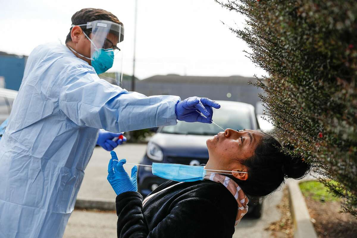 Dentist Dr. Marco Reyes (left) gives patient Daisy Rios-Rojas (right) a Covid-19 test in San Francisco, California on Thursday, April 9, 2020. A small tent in the Southeast Health Center parking lot was serving as an alternative testing site for potential COVID-19 cases. Patients who are tested have been pre-screened by a health care provider.
