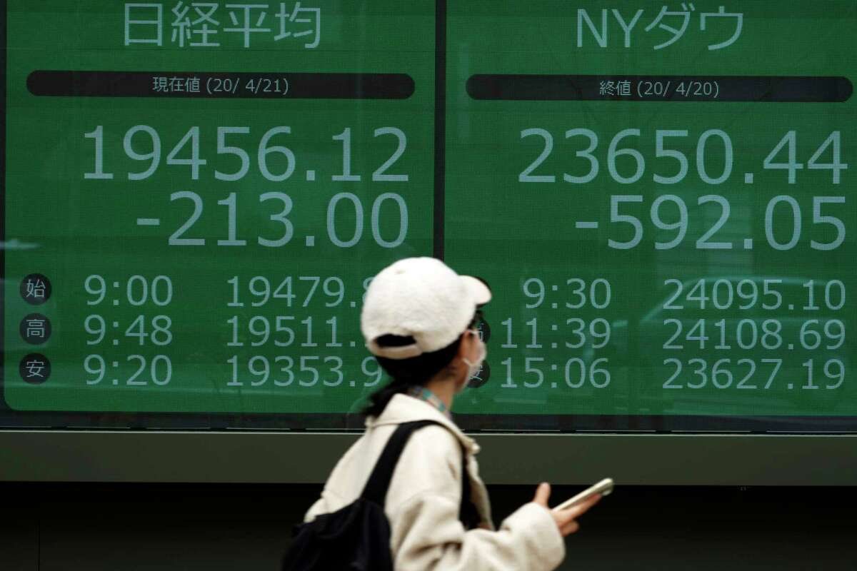 A woman wearing a mask against the spread of the new coronavirus walks past an electronic stock board showing Japan's Nikkei 225 and New York Dow index at a securities firm in Tokyo Tuesday, April 21, 2020. Asian shares skidded on Tuesday after U.S. oil futures plunged below zero as storage for crude runs close to full amid a worldwide glut as demand collapses due to the pandemic. (AP Photo/Eugene Hoshiko)