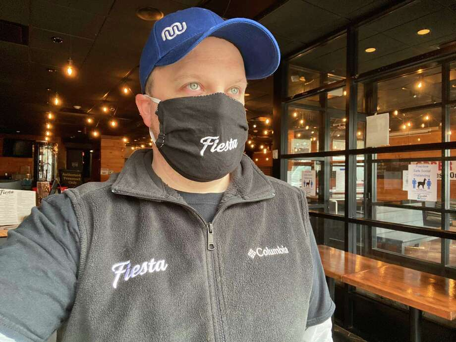 Victor Mathieu, co-owner of Fiesta on Main restaurant in downtown Stamford, Conn., wears a mask inside the restaurant. When it re-opens on Thursday, April 23, the restaurant will require customers picking up orders to wear masks in the premises. Photo: Contributed Photo