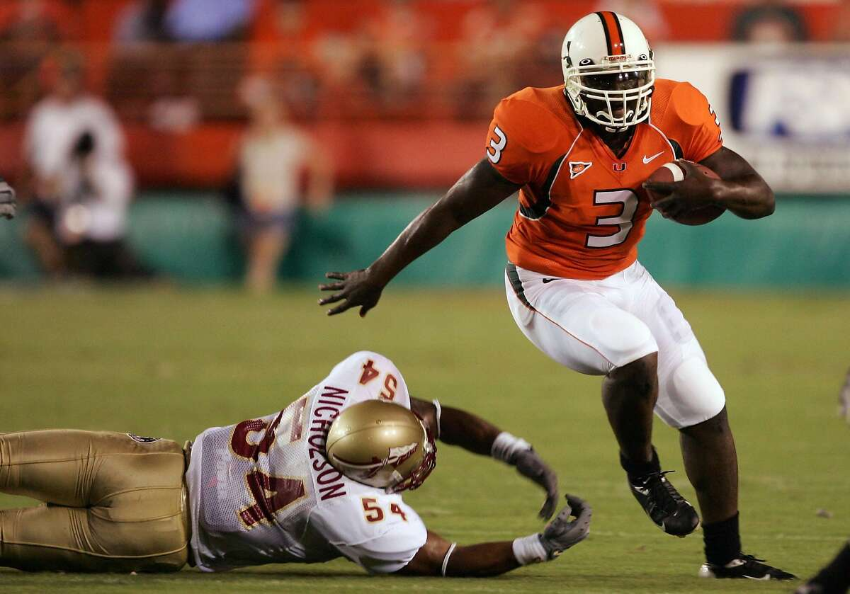 MIAMI - SEPTEMBER 10: Frank Gore #3 of the University of Miami Hurricanes runs with the ball as A.J. Nicholson #54 of the Florida State Seminoles tries to block him in the first half on September 10, 2004 at the Orange Bowl Stadium in Miami, Florida. ~~