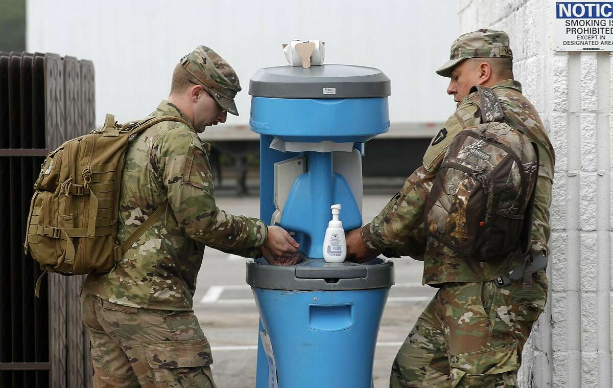 Soldiers with the National Guard wash their hands before entering the Montgomery County Food Bank in Conroe.