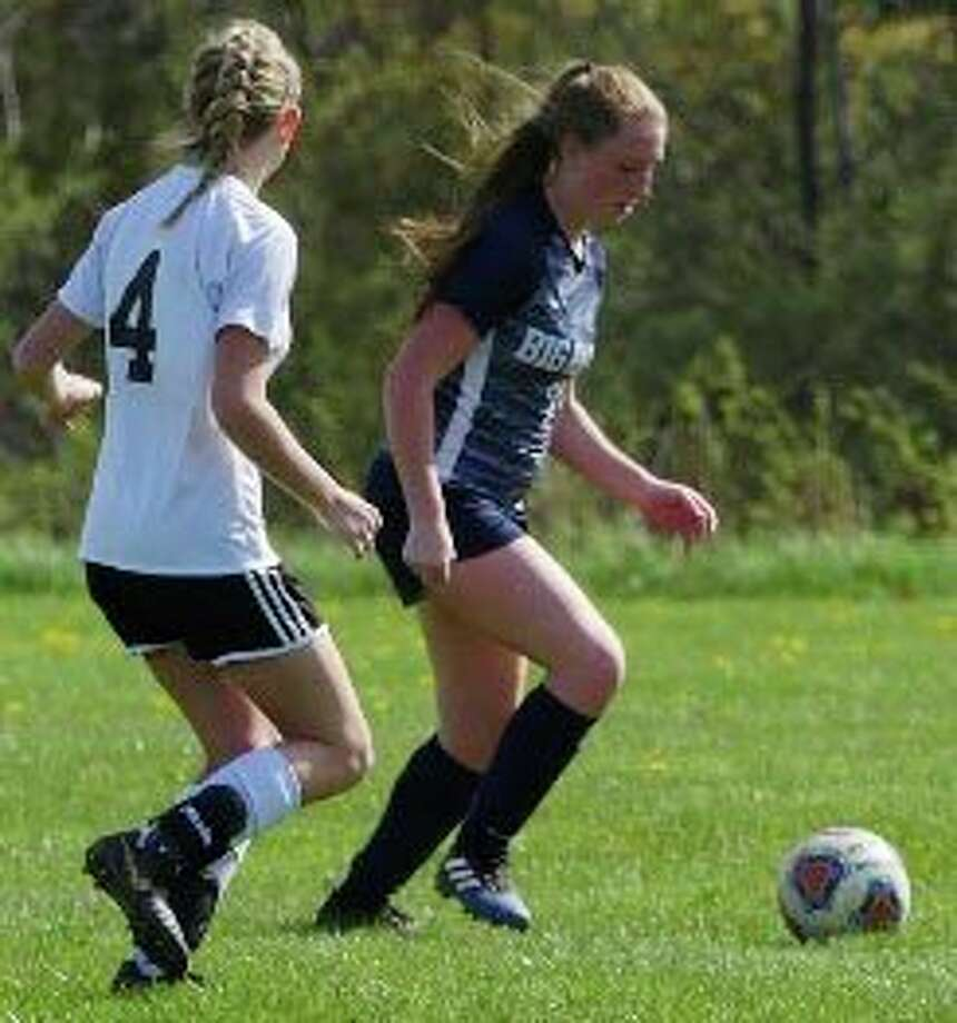 Big Rapids' Chloe Miller (right) goes after the ball in soccer action in a previous season. (Courtesy photo)