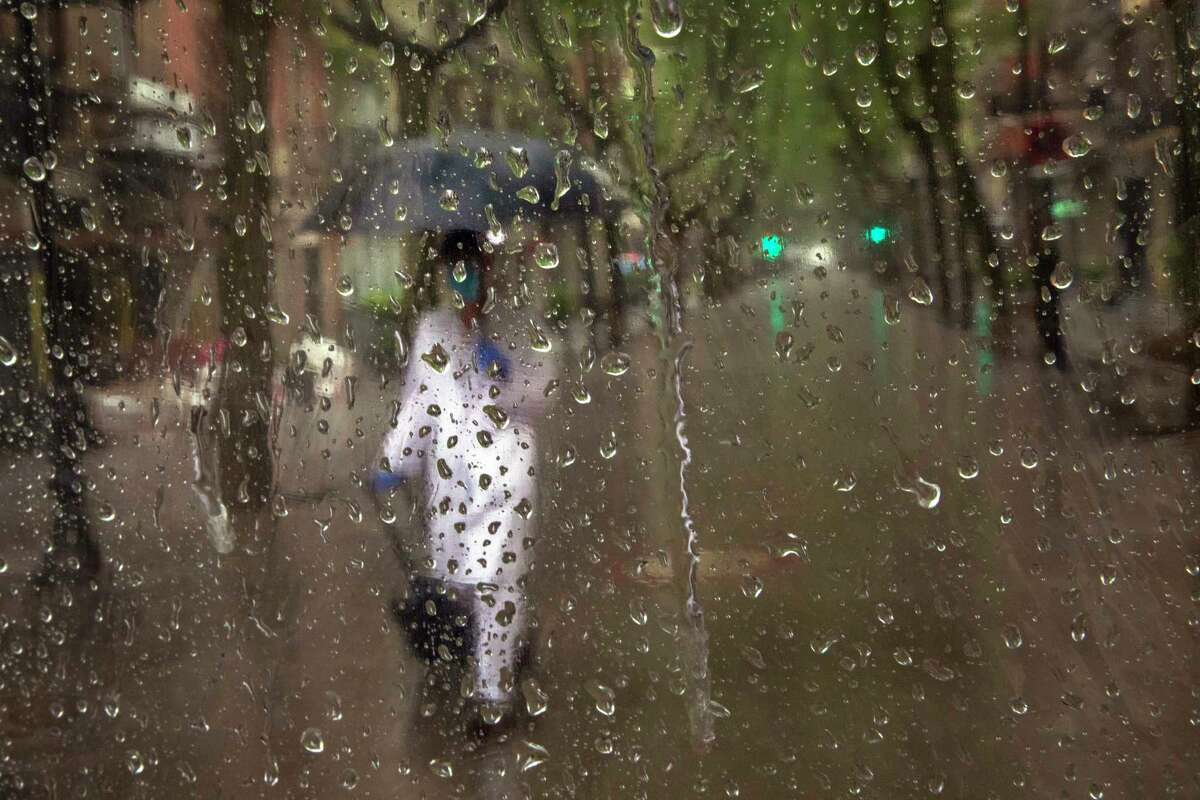 A primary care physician walks to visit a patient during a rainfall in Barcelona, Spain, Tuesday, April 21, 2020, as the lockdown to combat the spread of coronavirus continues. (AP Photo/Emilio Morenatti)