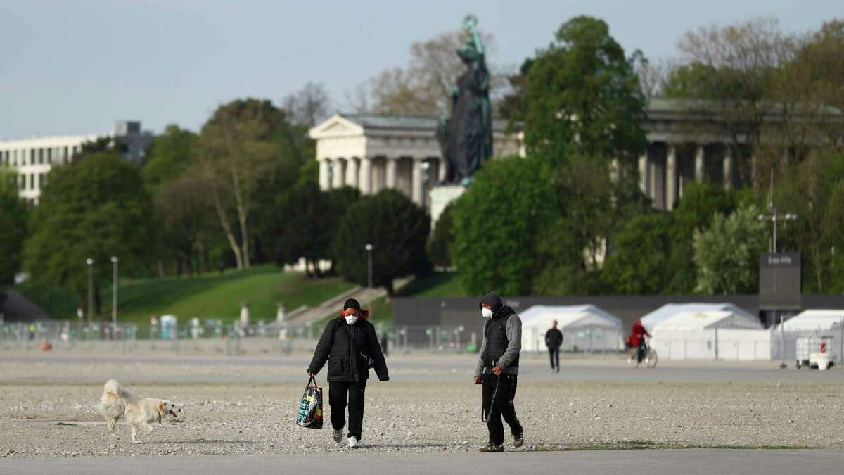 People wearing protection masks as they across the 'Theresienwiese', the Oktoberfest beer festival area, in Munich, Germany, Tuesday, April 21, 2020. Bavarian state governor Markus Soeder and Munich mayor Dieter Reiter announced at a news conference that the Oktoberfest is cancelled this year because the coronavirus outbreak. (AP Photo/Matthias Schrader)