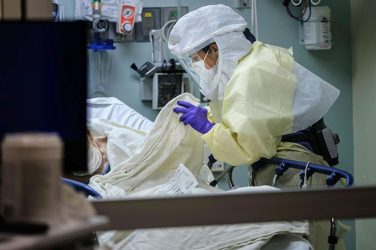 Wearing personal protective equipment, nurse April Bandi cares for a patient under investigation with possible COVID-19 symptoms inside a special negative pressure isolation room at the Emergency Department at Sharp Memorial Hospital on April 10, 2020 in San Diego, Calif. (Marcus Yam/Los Angeles Times/TNS)