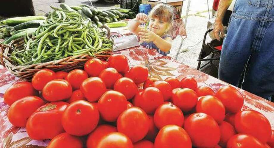 Marley Beilsmith, 4, of Jerseyville, plays with a green bean as she helps her grandfather, Bob Sancamper, at his produce stand in the Alton farmer's market on the parking lot at the foot of Henry Street in Alton, last year. Photo: John Badman | Telegraph File Photo
