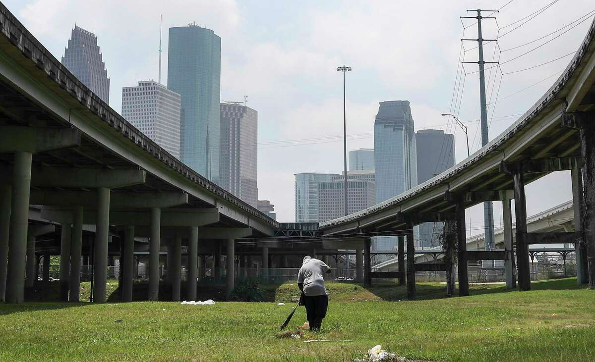 Pete Ward rakes up pieces of trash under IH-45 on Tuesday, April 21, 2020, near his home in Houston.