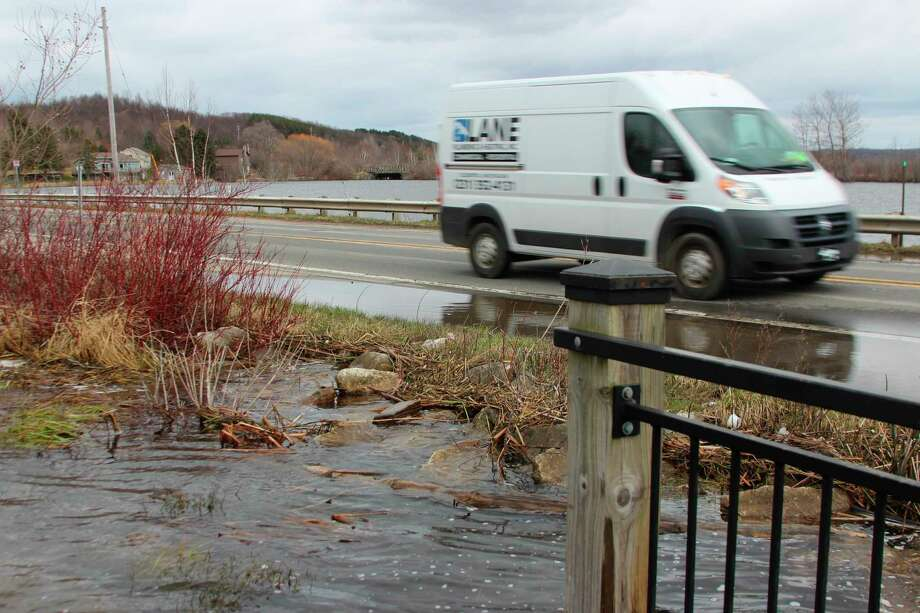 (ABOVE) High water and waves push Betsie Bay up to the edge of the causeway between Frankfort and Elberta. (LEFT) Water crashes over the breakwall at Elberta on during a period of strong winds. (Photos/Colin Merry)