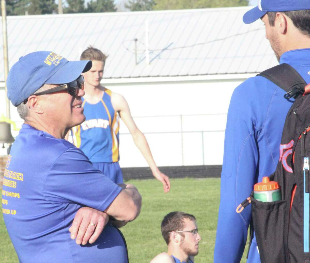 Evart's Dennis Peacock (left) has a discussion on the track sidelines duringa meet last year.(Herald Review photo/John Raffel)