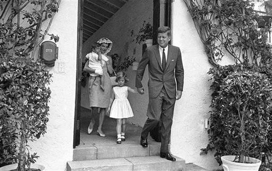 President John F. Kennedy and Mrs. Jacqueline Kennedy as they left the home of the presidents father, where they attended a private family mass in Palm Beach, Florida on April 22, 1962. Mrs. Kennedy carries John F. Jr., bare footed as the president holds Caroline by the hand. (AP Photo)