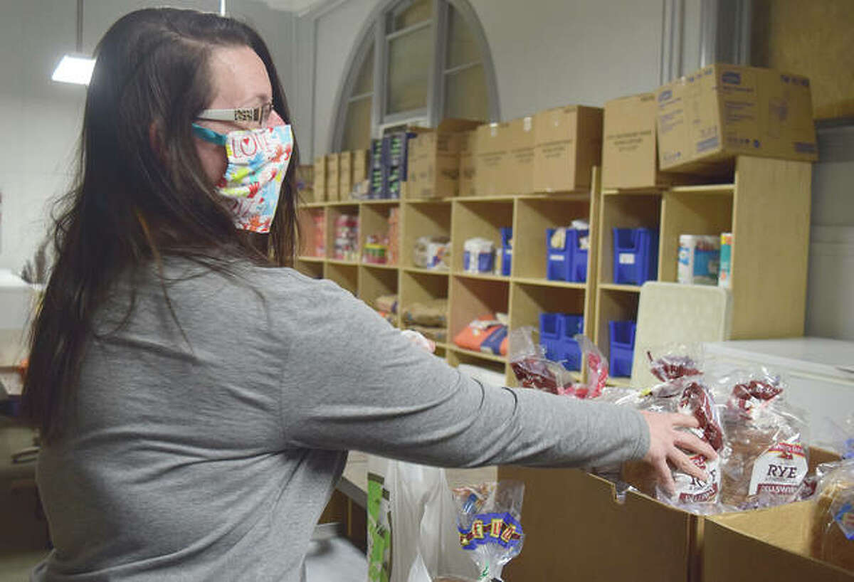 Christy Martin, assistant administrator for the Jacksonville Area Community Food Center, prepares food for pick-up Tuesday.