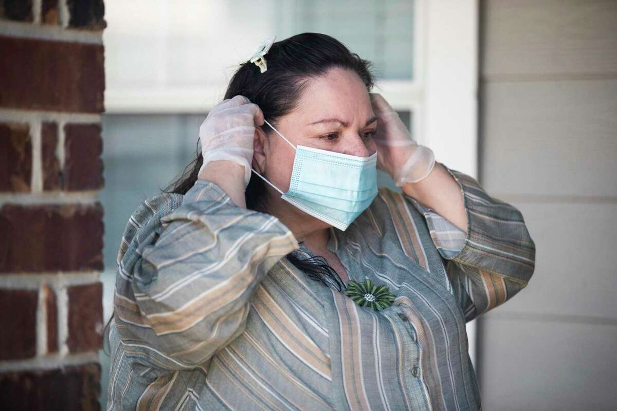 Estela Fuentes, 53, fixes a protective mask at her home on Thursday, April 16, 2020, in Houston. Fuentes is a kidney transplant patient who got COVID-19 mid March and was hospitalized about 12 days. Fuentes accepted an experimental treatment while she was hospitalized at Baylor St. Luke's.