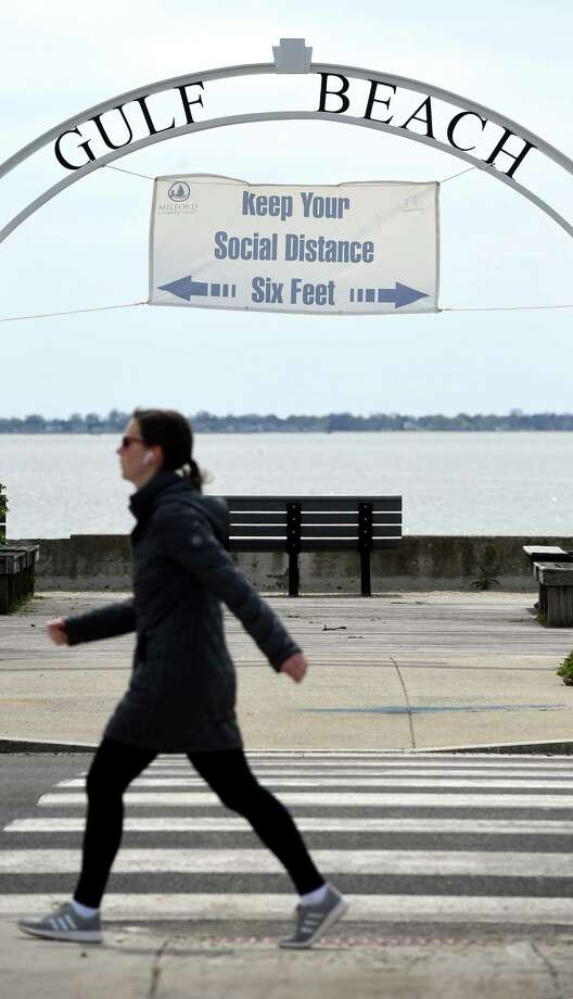 A woman walks past Gulf Beach in Milford where a sign encourages social distancing on April 20, 2020. Photo: Arnold Gold / Hearst Connecticut Media / New Haven Register