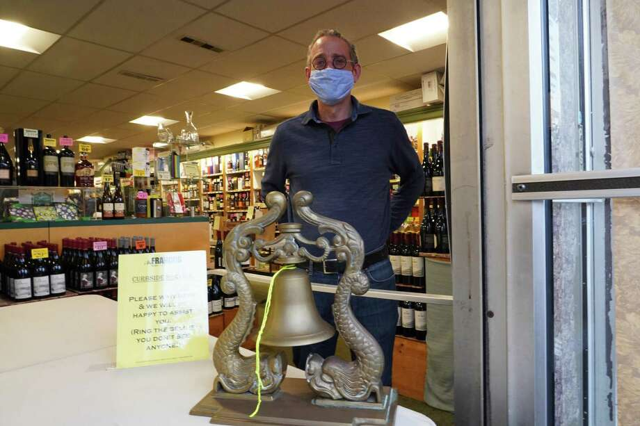 Carl Franco said he was smiling for a picture underneath his mask on Tuesday, at the front of Francos Liquor Store at 130 Elm Street in New Canaan. Photo: Grace Duffield / Hearst Connecticut Media