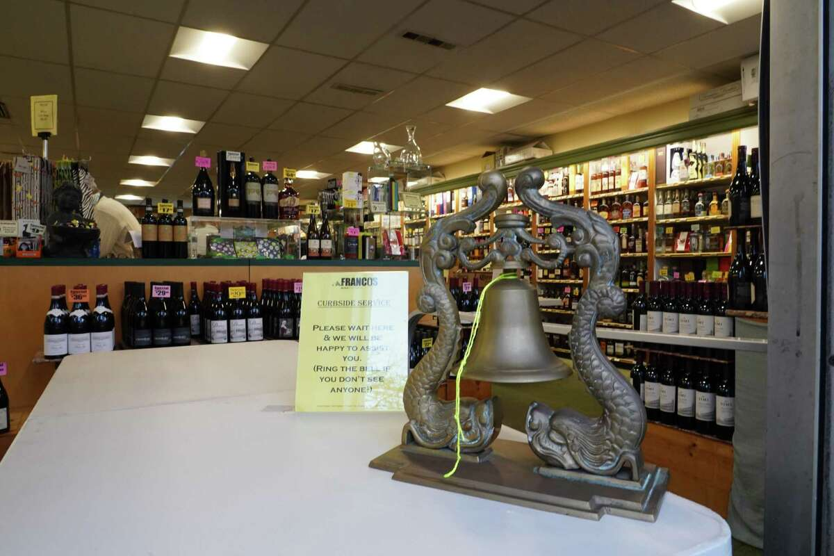 Francos Liquor Store at 130 Elm Street in New Canaan is adapting to the new ways of doing business during the coronavirus crisis. People are asked to ring the bell for service when needed.