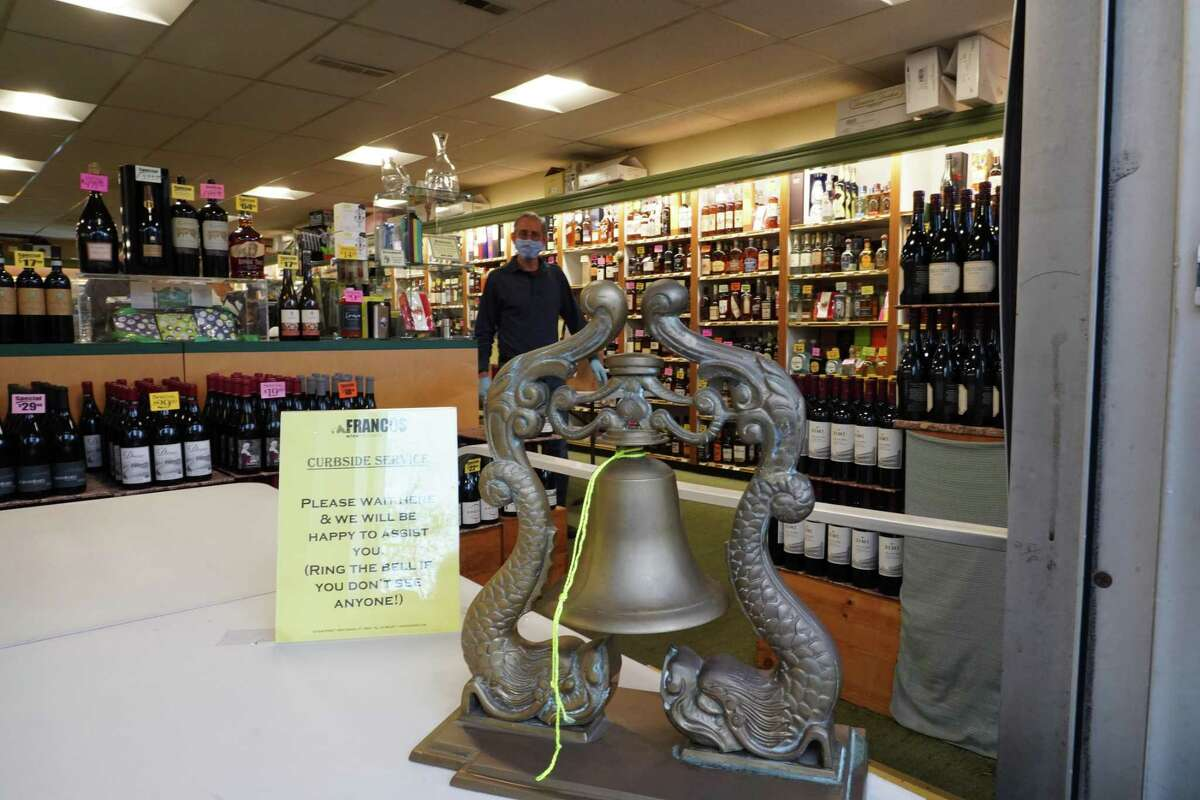 People are asked to ring the bell for service at Francos Liquor Store at 130 Elm Street in New Canaan as the store adapts to the new ways of doing business during the coronavirus crisis.