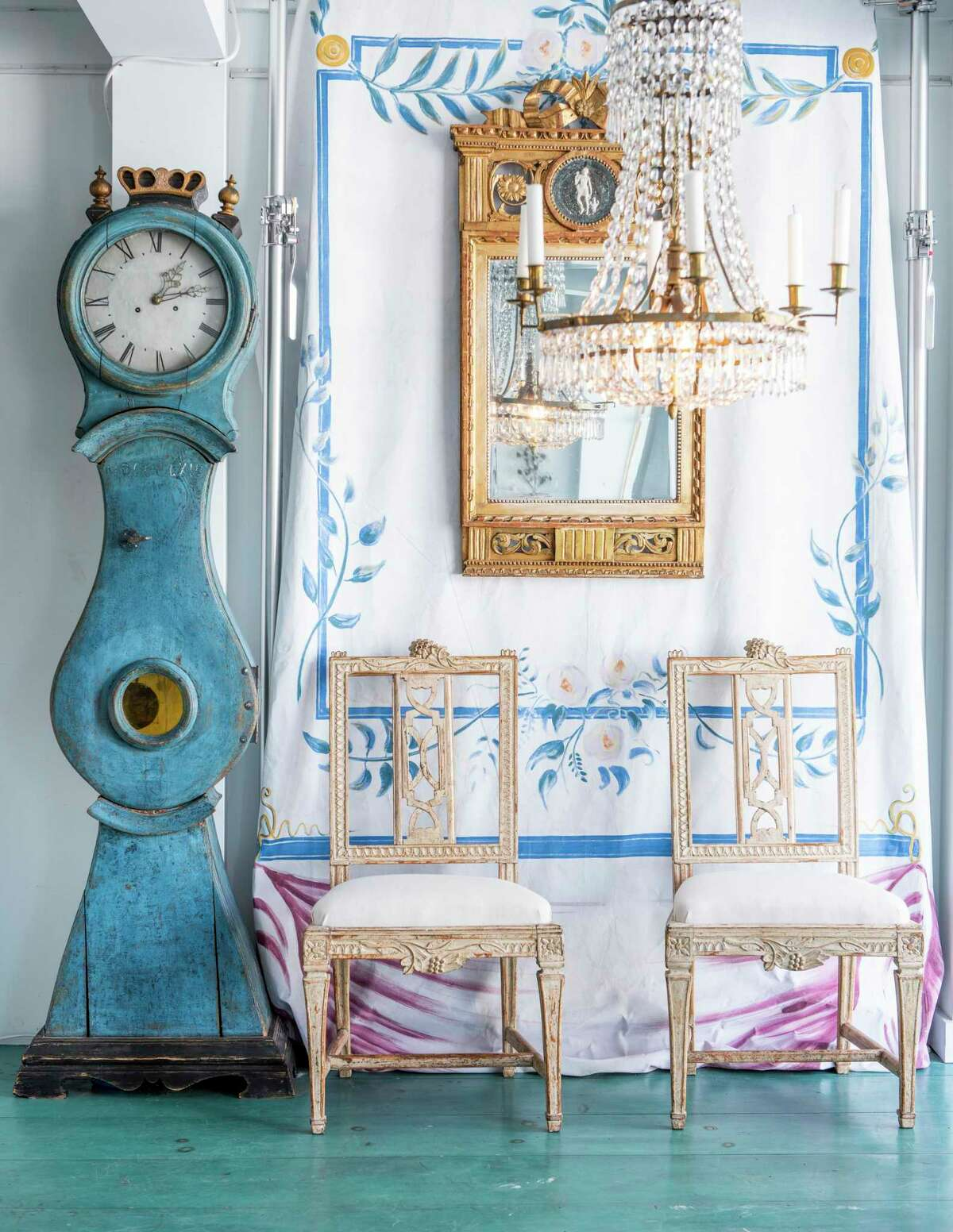 A display at Dawn Hill Antiques in New Preston features a painted panel depicting wall paintings typically found in 18th century Swedish rooms, a Gustavian period Swedish mirror, a Swedish blue painted Mora clock, and a Swedish chandelier; the two chairs are a pair of Swedish Lindome dining chairs, circa 1790.