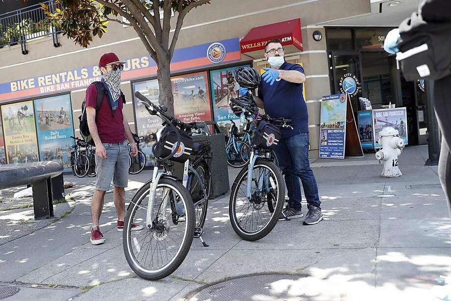 Andrew Foy goes through rental guidelines with customers, Tyler Hausman Carver (left) and Scarlette Tidy, at Bay City Bike Rentals on Bay Street  in San Francisco, Calif., on Tuesday, April 21, 2020. Photo: Scott Strazzante / The Chronicle