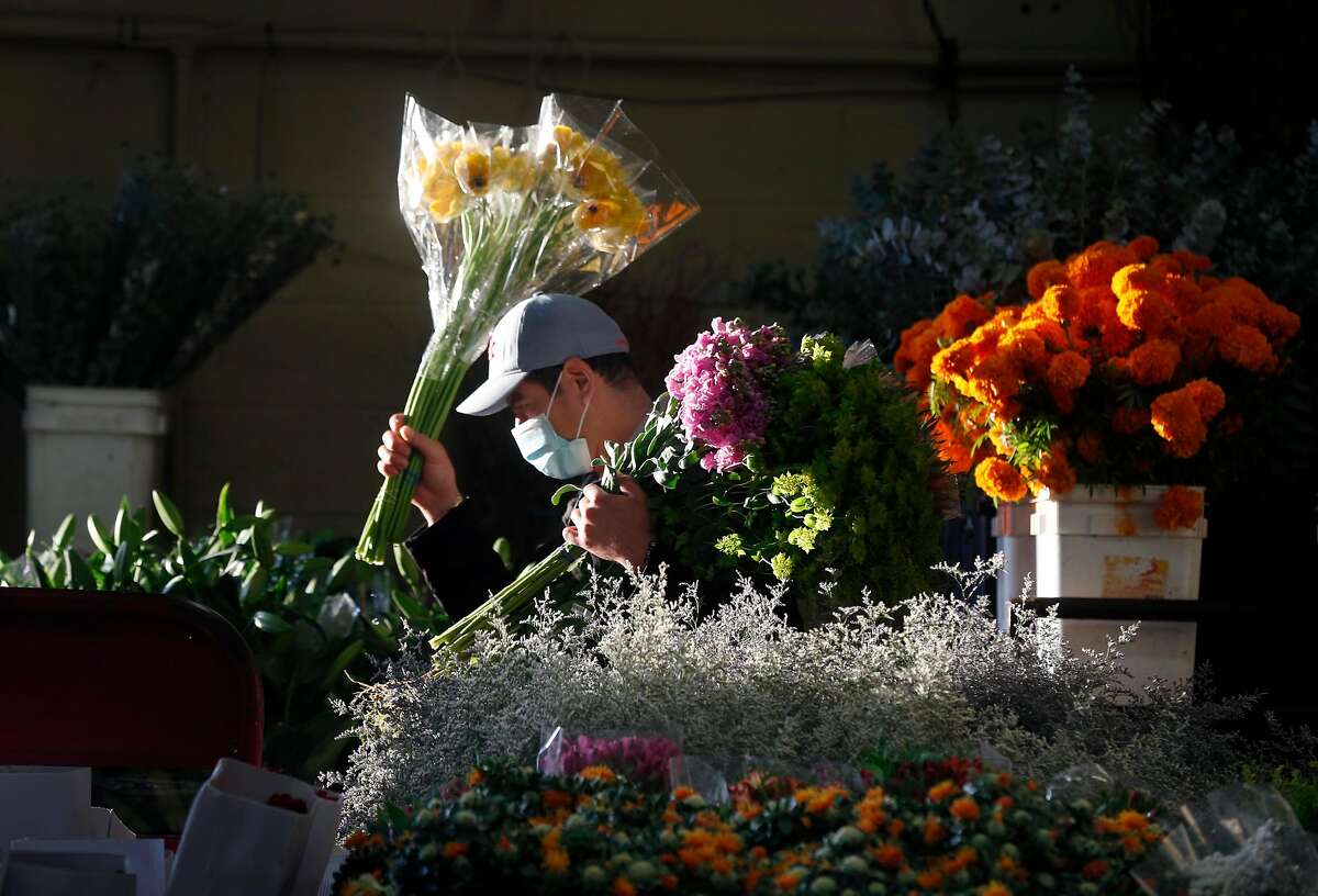An employee carries bunches of flowers through the Flower Mart which reopened in San Francisco, Calif. on Wednesday, April 22, 2020 after the city allowed the market to reopen with limited operations while the shelter in place orders remain in effect during the coronavirus pandemic.