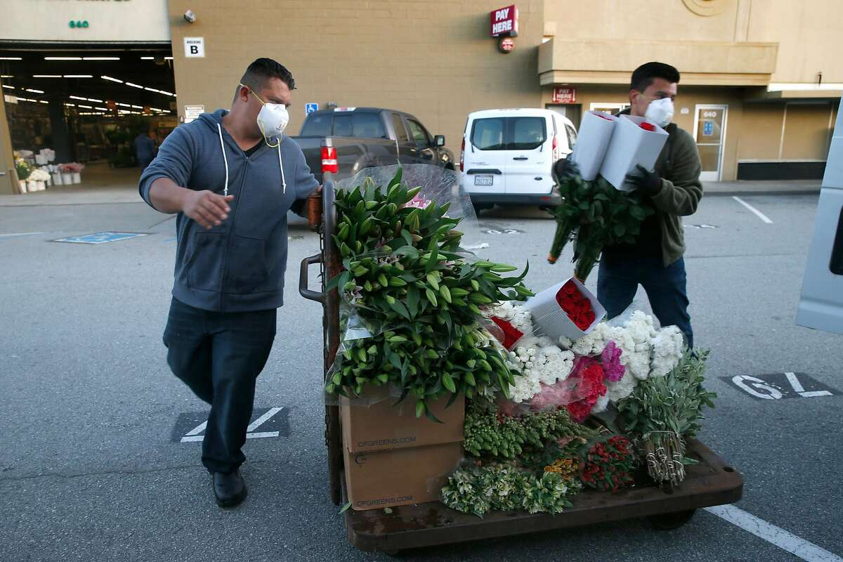 Ben Pabon (left) and his brother Tony Pabon load flower bunches into a customer's vehicle at the Flower Mart which reopened for modified business in San Francisco, Calif. on Wednesday, April 22, 2020 after the city allowed the market to reopen with limited operations while the shelter in place orders remain in effect during the coronavirus pandemic.