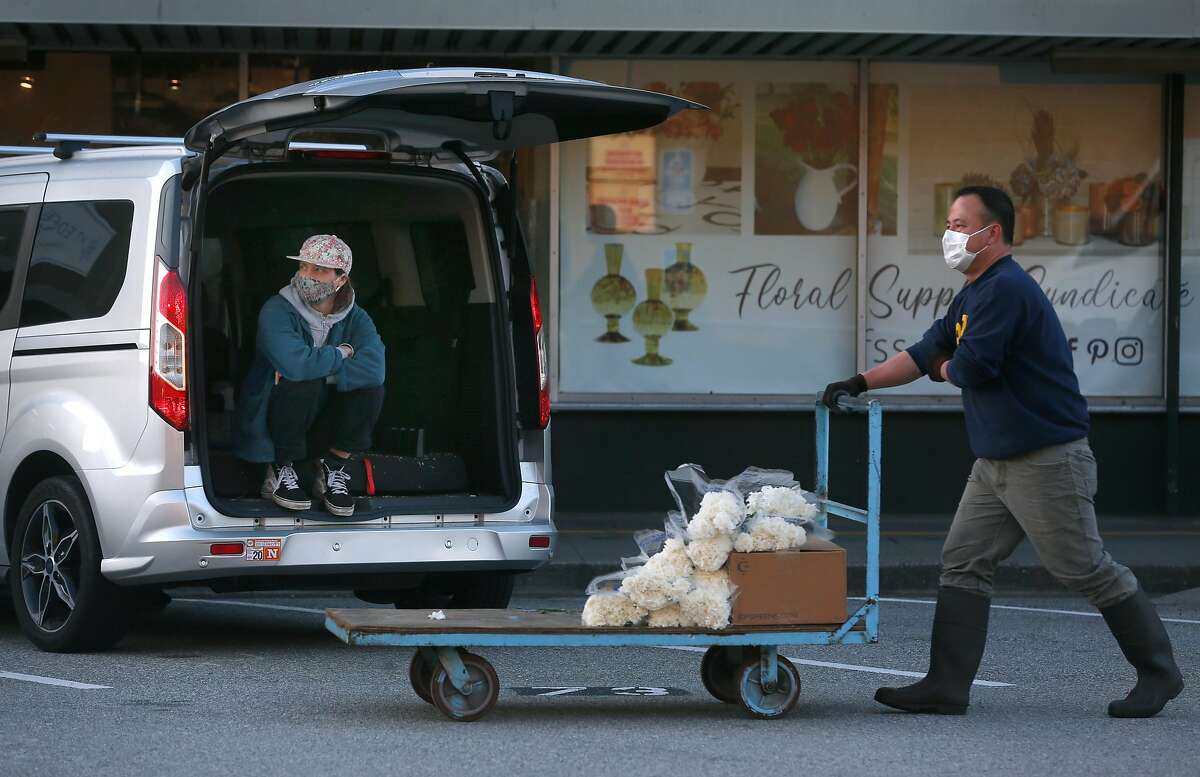 Charlotte Cox (left) waits for her order to be delivered to her car after modified business resumed at the Flower Mart in San Francisco, Calif. on Wednesday, April 22, 2020 after the city allowed the market to reopen with limited operations while the shelter in place orders remain in effect during the coronavirus pandemic.
