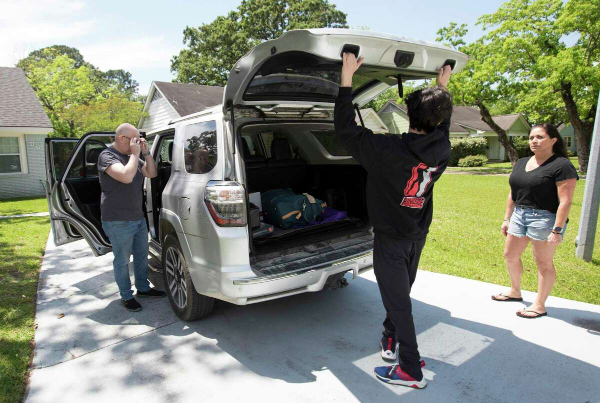 Sylvia Escobedo watches son, Luke Newman, 14, puts his luggage into the trunk while Murray Newman is picking Luke up to stay with him for a week Wednesday, April 15, 2020, at Garden Oaks in Houston. Murray and Escobedo have modified the custody of Luke by alternating weeks during the coronavirus, and both have found the process to be as smooth as it has before the pandemic. Before the pandemic, Newman almost sees Luke everyday while Luke lives with Escobedo.