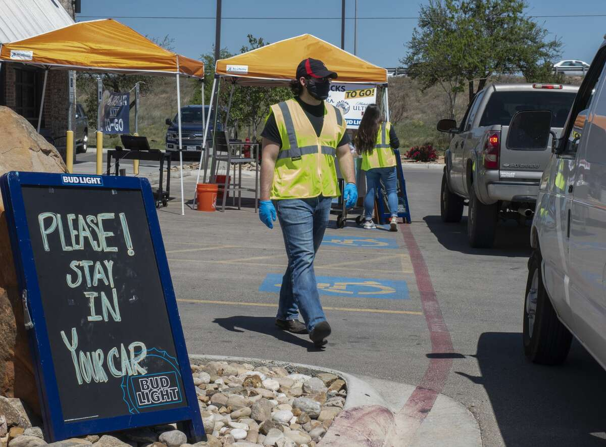 """Bubba's 33 staff take orders and deliver food 04/22/2020 in their """"drive-thru"""" outside the store. Bubba's 33 is donating 10% of sales to local hospital staff for PPE, personal protective equipment. Tim Fischer/Reporter-Telegram"""