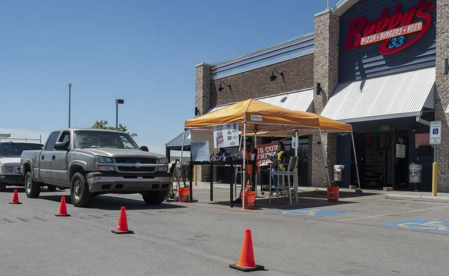 "Bubba's 33 staff take orders and deliver food 04/22/2020 in their ""drive-thru"" outside the store. Bubba's 33 is donating 10% of sales to local hospital staff for PPE, personal protective equipment. Tim Fischer/Reporter-Telegram Photo: Tim Fischer/Midland Reporter-Telegram"