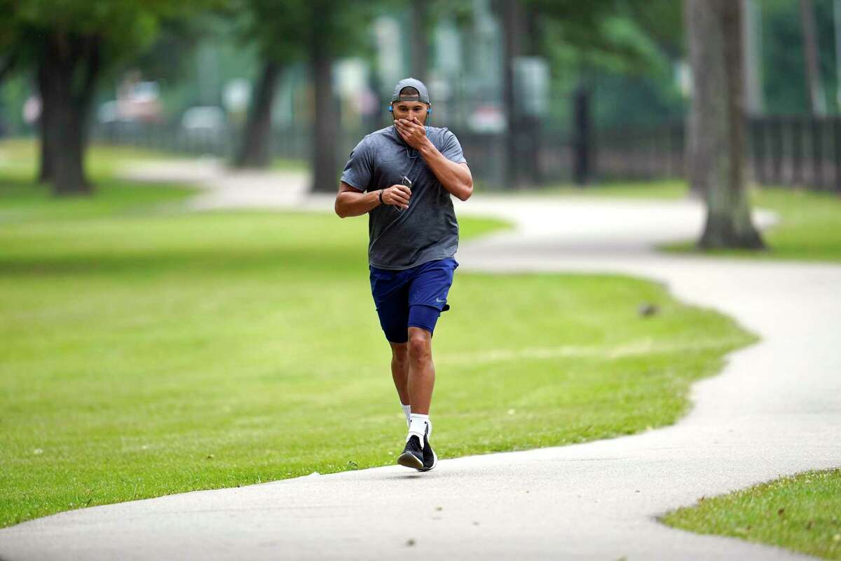 A jogger wipes his face as he runs at a Harris County park Wednesday, April 22, 2020, in Spring, Texas. Harris County Judge Lina Hidalgo is expected to announce an order Wednesday for residents to cover their faces in public to slow the spread of COVID-19. (AP Photo/David J. Phillip)