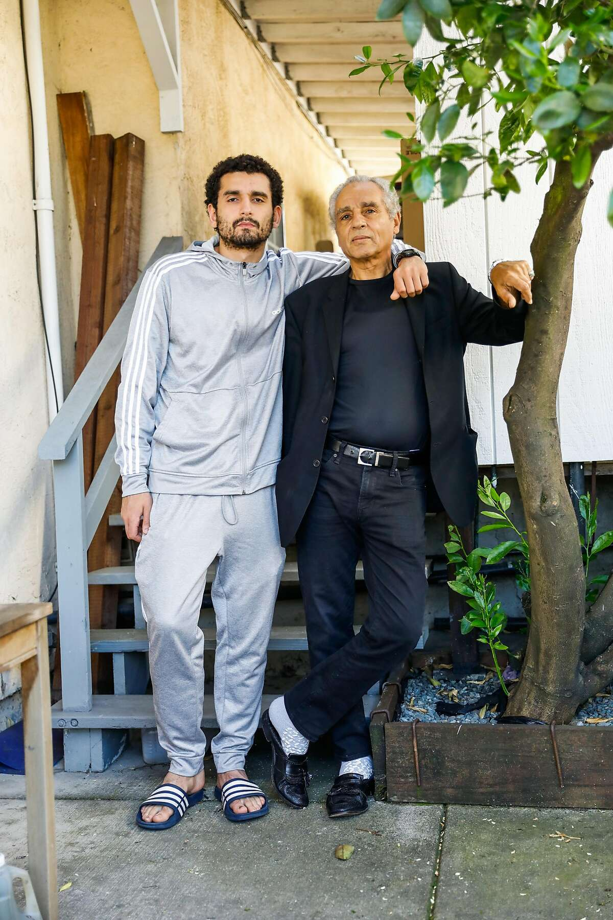 Hany Metwally, who had open heart surgery two weeks ago poses for a photo with his son Mohammed Metwally, 22, (left) outside of their home on Wednesday, April 22, 2020 in Oakland, California.
