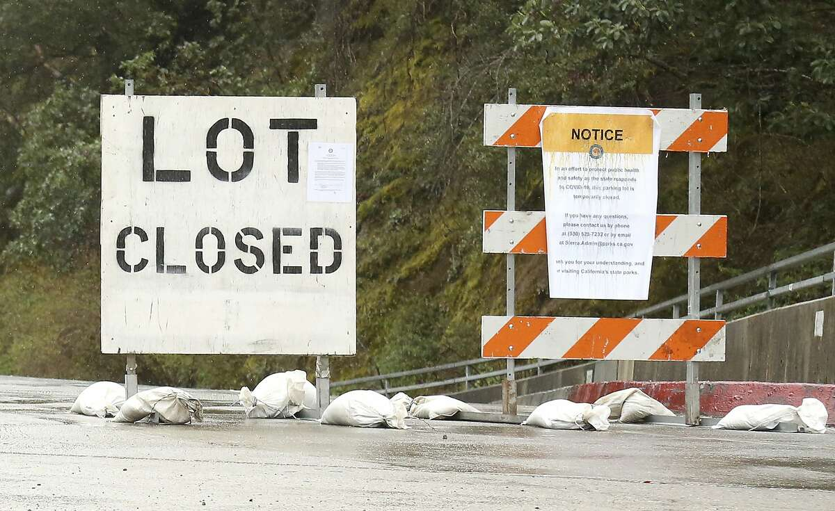 Signage lets people know of the Sierra District California State Park parking lot closures in Nevada City intended to help discourage large groups of people gathering in high traffic places due to the coronavirus, Saturday, March 28, 2020. (Elias Funez/The Union via AP)
