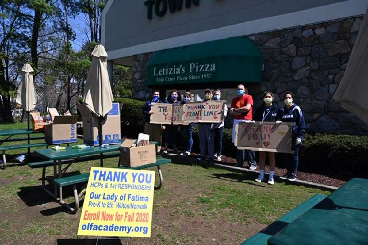 Members of Our Lady of Fatima Catholic Academy join Denis Letizia of Letizia's Pizza to thank healthcare workers.