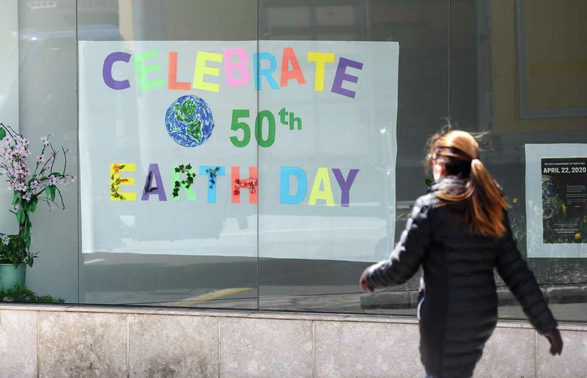 A woman passes by a sign commemorating the 50th anniversary of Earth Day at the former Tesla showroom in downtown Greenwich, Conn. Wednesday, April 22, 2020.