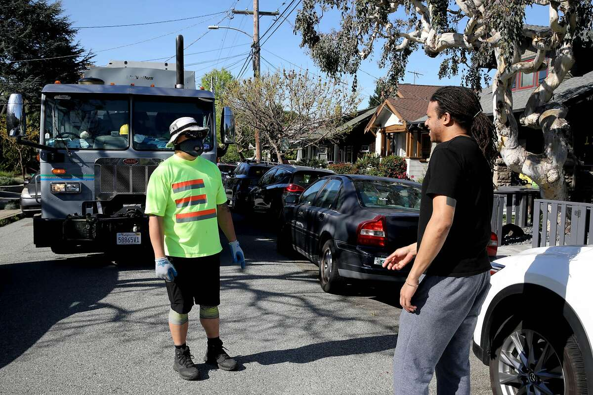 """Alvin Aragon, 50, left, talks with The Chronicle's Otis Taylor while working in the Rockridge neighborhood on Wednesday, April 22, 2020, in Oakland, Calif. Aragon drives a truck for California Waste Solutions, which handles Oakland's recycling contract. Aragon, who was raised in Oakland and is now raising his family in the city, says he touches about 1,000 containers a day. Sanitation and recycling loads have increased since we were told to stay inside. We're told to watch what we touch, but workers like Aragon put their hands on the containers filled with stuff we've discarded. We touch everything,"""" he said. Aragon's worried about getting his family sick. He wears plastic gloves under his work gloves. He washes off before leaving work and then takes a shower when he gets home."""