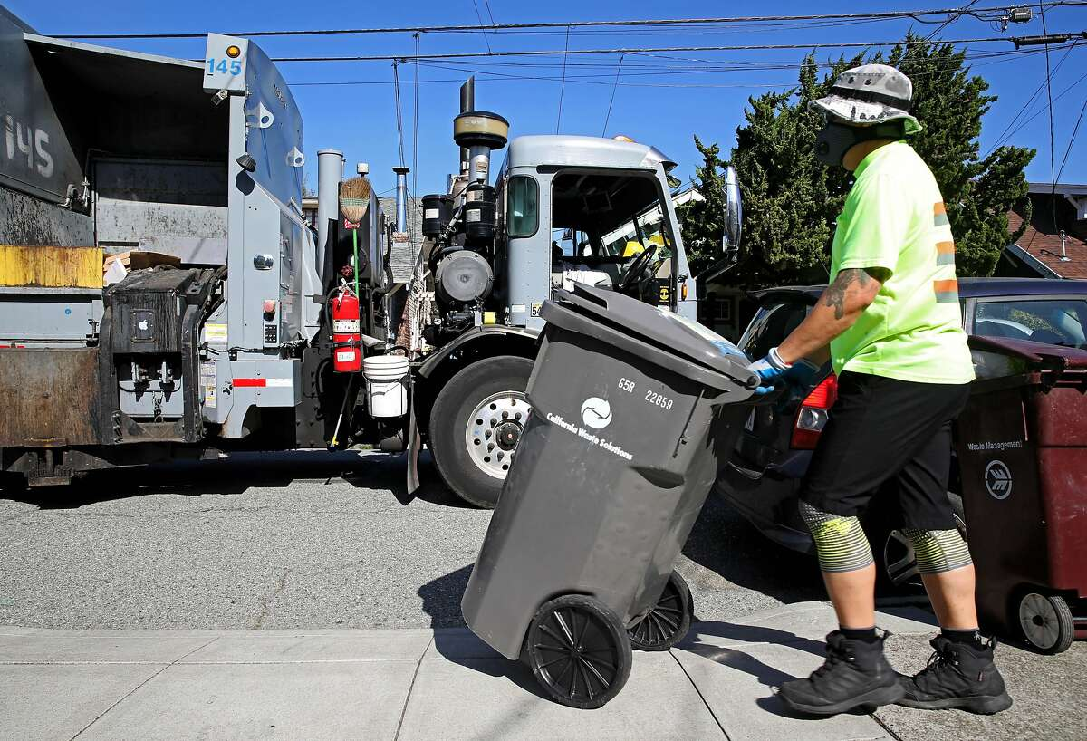 """Alvin Aragon, 50, collects a recycles bin as he works in the Rockridge neighborhood on Wednesday, April 22, 2020, in Oakland, Calif. Aragon drives a truck for California Waste Solutions, which handles Oakland's recycling contract. Aragon, who was raised in Oakland and is now raising his family in the city, says he touches about 1,000 containers a day. Sanitation and recycling loads have increased since we were told to stay inside. We're told to watch what we touch, but workers like Aragon put their hands on the containers filled with stuff we've discarded. We touch everything,"""" he said. Aragon's worried about getting his family sick. He wears plastic gloves under his work gloves. He washes off before leaving work and then takes a shower when he gets home."""