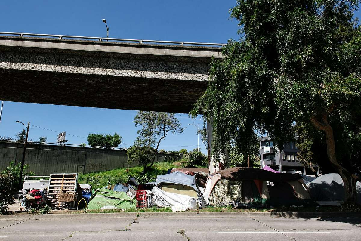 Tents and belongings are seen at a homeless encampment underneath Interstate 580 in Oakland, Calif, on Friday, April 22, 2020.