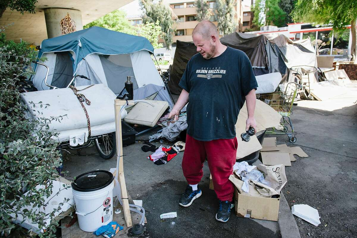 Nick Becker, points out a soap and water washing station that was donated by nearby neighbors at the homeless encampment underneath Interstate 580 where he has lived for the last 2 1/2 years, in Oakland, Calif, on Friday, April 22, 2020. Nick said that county officials that have visited the encampment have only offered quarantine shelter beds to people that are presenting symptoms of Covid-19.