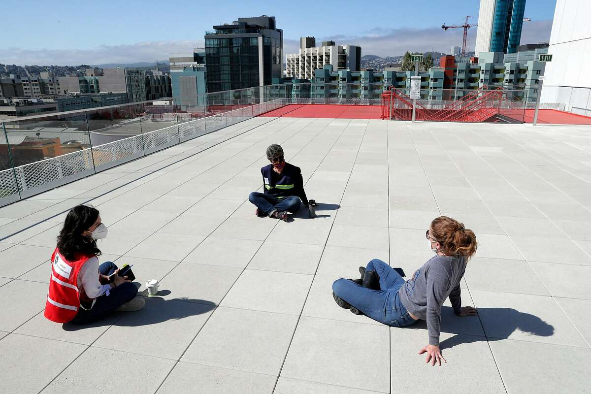 Rachel Cukierman, right, Rebecca Sherman, left, and Debbie Raphael, top, hold a meeting on the rooftop for their work with the Department of Human Resources Department Operations Center, at George R. Moscone Convention Center South where the Emergency Operations Center for the city has replaced city hall.