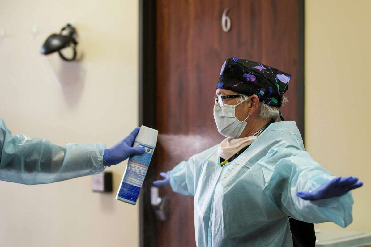 Registered nurse Krista Rozell is sprayed down with disinfectant after completing a preliminary examination of a patient at Texas Emergency Care Center on Wednesday, April 22, 2020 in Atascocita. The Trump administration approved Tuesday to allow freestanding emergency rooms in Texas to apply for certification as a Medicaid-certified hospital.