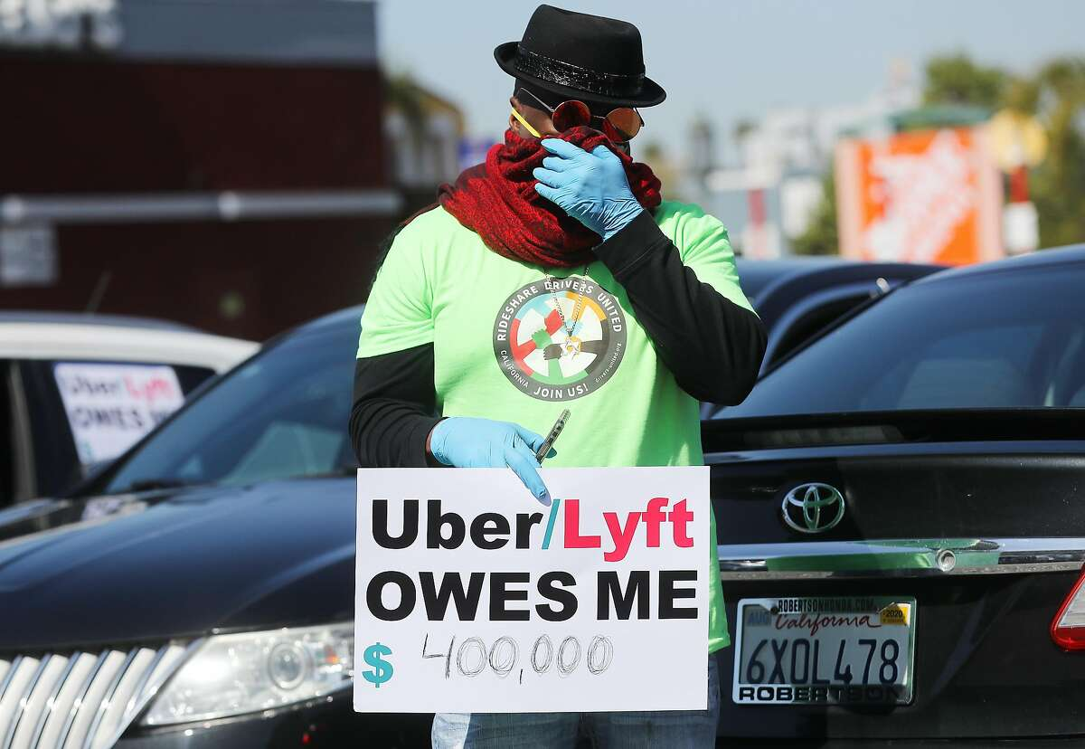 LOS ANGELES, CALIFORNIA - APRIL 16: A protestor displays a sign as Uber and Lyft drivers with Rideshare Drivers United and the Transport Workers Union of America prepare to conduct a caravan protest outside the California Labor Commissioners office amidst the coronavirus pandemic on April 16, 2020 in Los Angeles, California. The drivers called for California to enforce the AB 5 law so that they may qualify for unemployment insurance as the spread of COVID-19 continues. Drivers also called for receiving back wages they say they are owed. (Photo by Mario Tama/Getty Images)